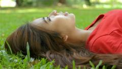 Young Asian woman relaxing, lying on the grass in a park Stock Footage