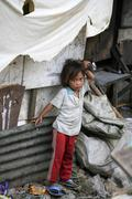 Stock Photo of child kid living in shantytown dwelling near tip