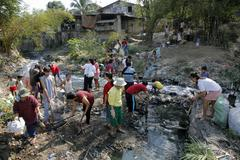 cleaning up filthy polluted stream in the slum - stock photo