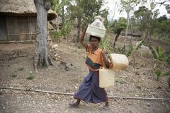 timor leste woman female carrying water by 2007 - stock photo