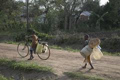 tanzania children kids carrying plastic to fetch - stock photo