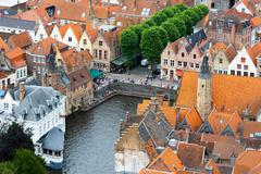 Roofs of flemish houses and canal in brugge, belgium Stock Photos