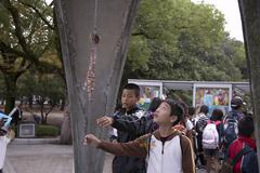 Japan school children kids at monument to atom Stock Photos