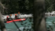 Two people in red canoe or kayak paddle through a river Stock Footage