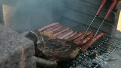 Picking the meat on a char-grilled grill with a big fork Stock Footage