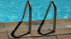 Swimming pool stairs in a pool on a sunny day Stock Footage