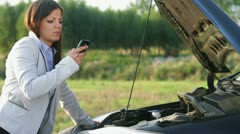 A woman calls for assistance after her car broke down HD Stock Footage