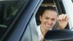 Young smiling woman with keys in a car HD - stock footage