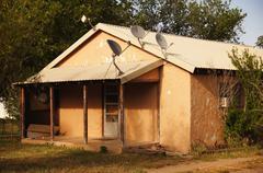adobe house satellite dishes dartboard meade tx - stock photo