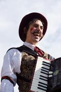 Music man male on stilts accordian laughing act Stock Photos
