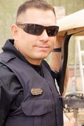 hispanic cop policeman officer portrait closeup - stock photo