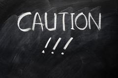 Caution written on blackboard Stock Photos