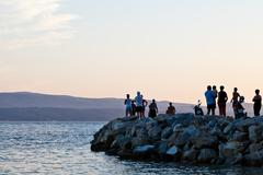 people on the pier looking at sunset in croatia - stock photo