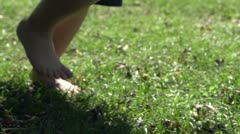 Feet running in grass tracking shot Stock Footage