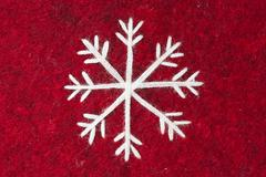 Red felt with embroidered white snowflake Stock Photos