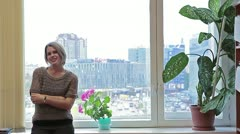 Woman near window speaking and looking at camera Stock Footage