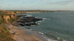 Cornwall coast with children playing in the surf at godrevy, cornwall Stock Footage