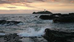 Godrevy lighthouse, cornwall with the sea hitting rocks at sunset Stock Footage