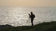Woman photographer with camera and tripod taking pictures of the sea Stock Footage