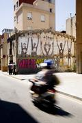 Motor driver and graffiti in the street of Barcelona. Spain. Stock Photos