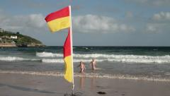 Children on the beach playing near safe bathing area red and yellow flags Stock Footage