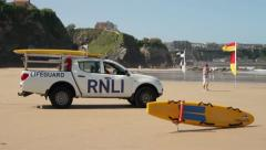 Rnli lifeguard vehicle and surfboard keeping watch over great western beach Stock Footage