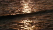 Golden waves gently rolling onto a beach at sunset Stock Footage