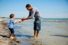 boy takes little steps towards his father - stock photo