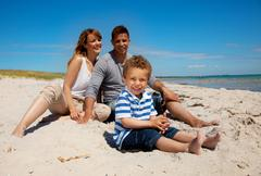 mixed race family looking happy on the beach - stock photo