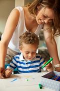 preschool teacher looking at the kid's drawing - stock photo