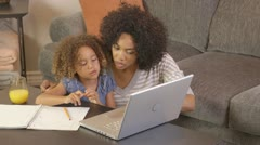 African American mother and daughter doing homework with laptop - stock footage