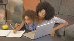African American mother and daughter doing homework with laptop Stock Footage
