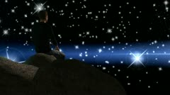 Man sitting on rock watching the night sky Stock Footage