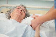 Nurse caring about old woman - stock photo