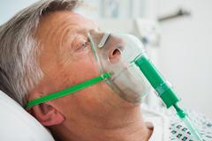 Man in bed with oxygen mask - stock photo
