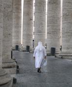Nun walking through colonnade Stock Photos