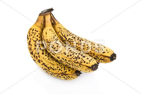 Stock photo of cluster of over ripe bananas isolated on white background