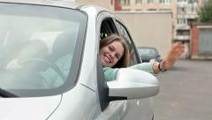 Cheerful woman looking out from car window - stock footage