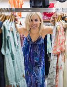 Nainen seisoo välillä vaatteita stand - stock photo