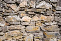 Old stone wall made with irregular blocks. - stock photo