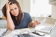 Stock Photo of Young woman looking worried over finances