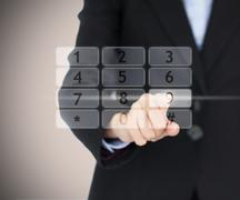 Stock Photo of Business woman entering code on digital number pad