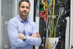 Man standing with arms crossed in data center Stock Photos