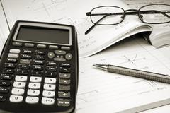 Scientific Calculator with exercise books and glasses - stock photo