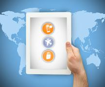 Person holding a tablet PC on world map background - stock photo