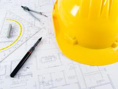 Building projects with architect drawing and protective tools - stock photo