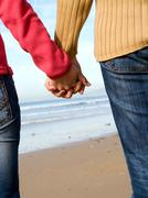 Lovers couple holding hands on beach at winter Stock Photos