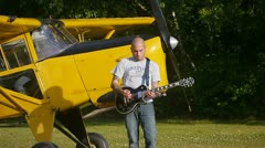 MAN PLAYING GUITAR BY AUSTER AIRPLANE Stock Footage