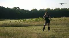 SEXY WOMAN ON GRASS RUNWAY PLANE LANDING Stock Footage