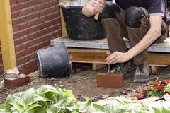 bricklayer breaking a brick - stock photo